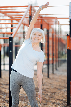 I am happy. Joyful blond woman smiling and exercising in the open air