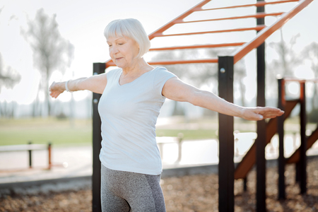 I feel great. Content blond woman smiling and exercising in the open air Stok Fotoğraf