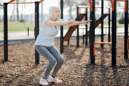 Determination. Concentrated aged woman doing squats and exercising in the open air