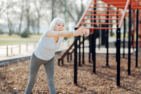 My great day. Delighted aged woman wearing sports clothes and exercising in the open air Stock Photo
