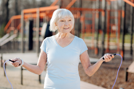 I am fit. Delighted thin woman jumping rope while exercising in the open air Stok Fotoğraf