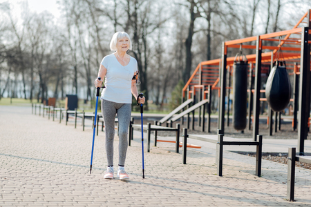 I love fitness. Delighted blond woman smiling and walking with the help of crutches Stok Fotoğraf
