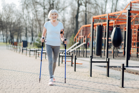 I like sport. Inspired blond woman smiling and walking with the help of crutches Stok Fotoğraf