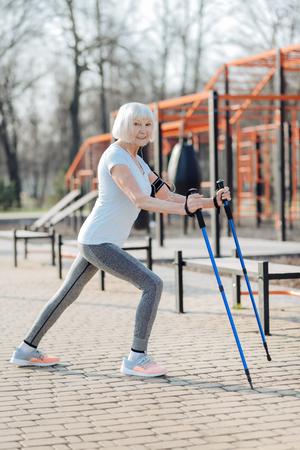 I like training. Joyful blond woman smiling and using crutches while exercising