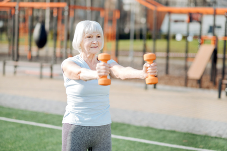 I am inspired. Alert slim woman holding hand weights while exercising in the open air