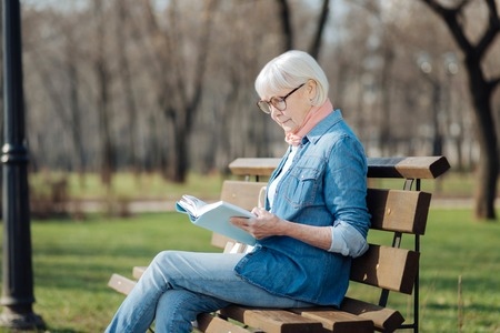 I love reading. Concentrated blond woman reading a book while sitting on the bench