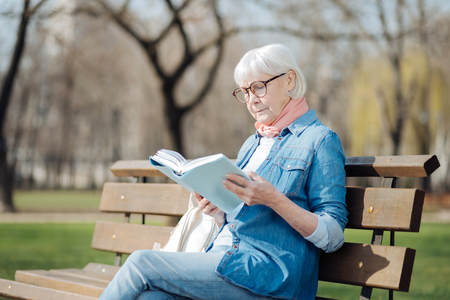 Avid reader. Involved blond woman reading a book while sitting on the bench Archivio Fotografico