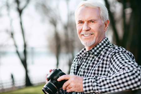 Photo skills. Appealing mature man utilizing camera and gazing at camera