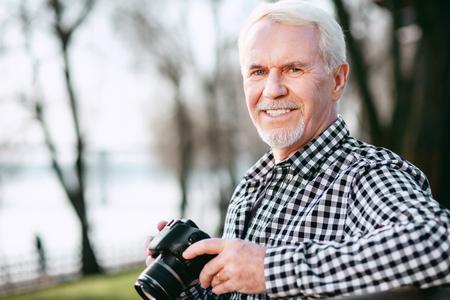Photo skills. Appealing mature man utilizing camera and gazing at camera 免版税图像 - 102002098