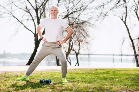 Healthy lifestyle. Energetic mature man working out in park and stretching