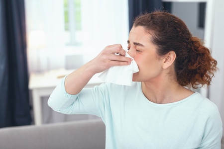 Achoo once more. Lady on a sick leave staying at home and having a runny nose as a result of suffering from a sudden burst of seasonal allergies Banco de Imagens