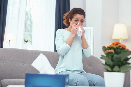 Influenza condition. Adolescent fair haired lady blowing her nose suffering from influenza while staying at home due to her illness