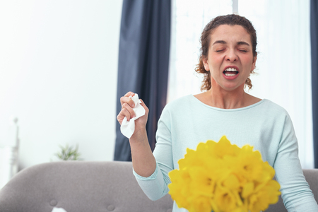 Home alone. Young woman looking sick feeling angry and tired of staying home being extremely allergic to flower pollen Stock Photo