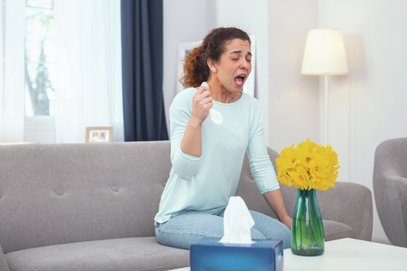Reason to sneeze. Young sick looking girl feeling upset and frustrated about her annoying flower pollen allergy Stock Photo