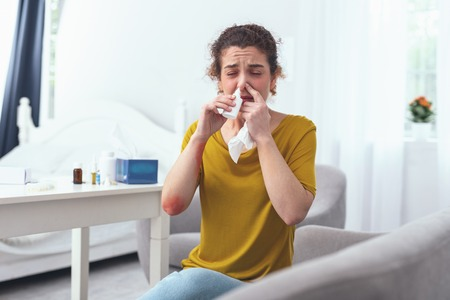 Cure for nose. Young curly woman sitting on a grey couch by the white table while using nasal spray for her runny nose