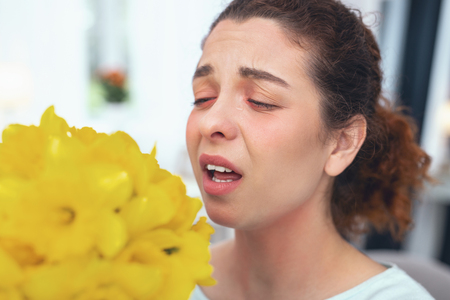 Unsuccessful present. Adolescent woman being presented a bouquet of flowers experiencing sudden symptoms of seasonal allergy to pollen Stock fotó