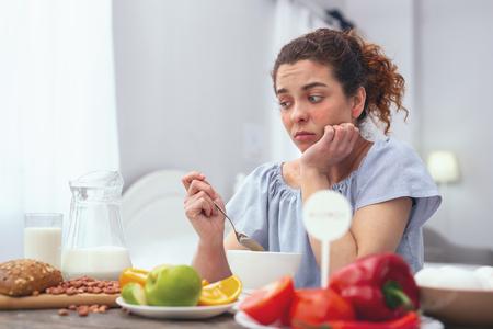 Appetitlosigkeit. Junge Frau, die an einem Frühstückstisch sitzt, einen Löffel hält und entmutigt aussieht, während sie versucht, sich zu zwingen, zu essen