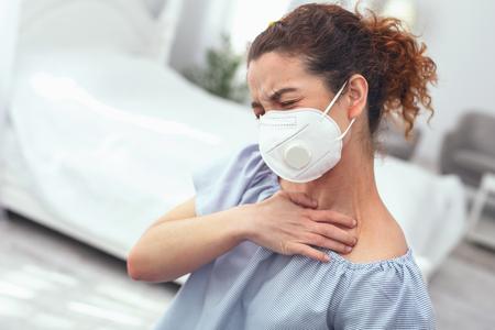 Condición agravada. Joven dama enferma aferrándose a su garganta sufriendo complicaciones causadas por la gripe Foto de archivo - 102002459