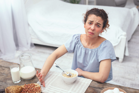Nut allergy. Young woman looking unhappy at a breafast table while refusing to eat nuts and nut containing bread with her oatmeal