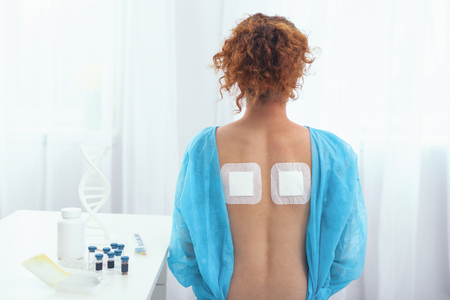 Pain relief. Young woman in a labcoat demonstrating a successful use of orthopedic bandaids having her back pain relieved