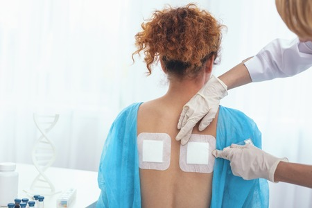 Back pain relieving. Young girl standing still receiving some heat plasters for her sore back being examined by a professional doctor Reklamní fotografie