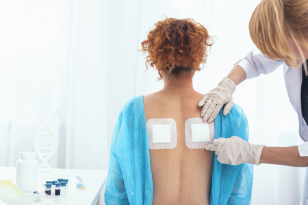 Proper treatment. Hospital patient having her back exposed to a doctor while getting some proper treatment for back pain
