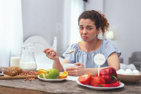 Food dissatisfaction. Adolescent woman looking unwell not enjoying her healthy nutricious meal due to suffering from an upset stomach