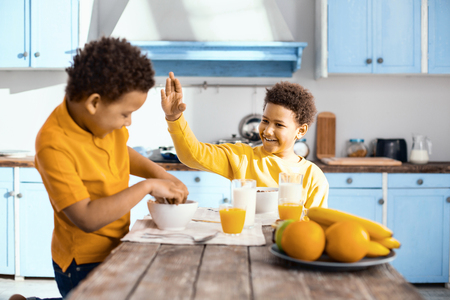 Behave yourself. Smiling pre-teen boy sitting at the table and raisin his hand as if to slap his little brother while he eating cereals with his hands Stock Photo
