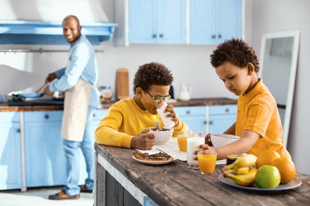 Morning routine. Charming little boys sitting at the table and having breakfast while their father cooking in the background