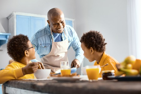 Happy family. Cheerful young man talking to his children and offering them omelet while they eating breakfast Foto de archivo
