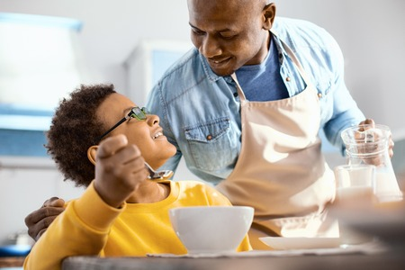 Sign of affection. Cheerful young father hugging his son and chatting with him while pouring him some milk into the glass