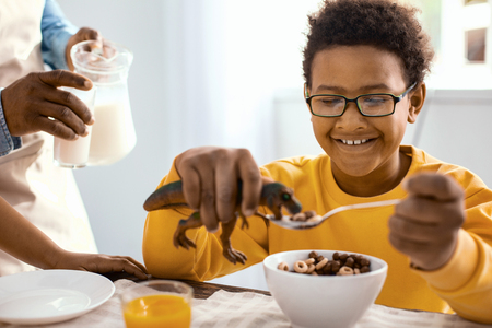 Enjoying himself. Pleasant upbeat boy playing with a toy dinosaur and feeding it with cereals while his father pouring him a glass of milk Stock Photo