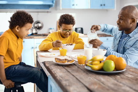 Great pastime. Pleasant young father talking to his sons during breakfast while pouring a glass of milk