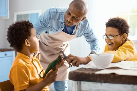 自分を振る舞ってください。彼らは周りにグーフと朝食中におもちゃで遊んでいる間、彼の小さな息子を落ち着かせようと愛する若い父親