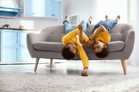 Playing around. Cheerful little brothers lying on the sofa upside down and tickling each other while laughing happily Stock fotó