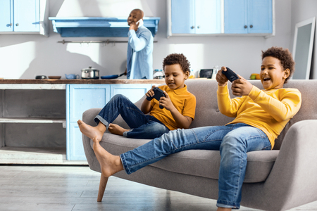 Avid gamers. Cheerful little boys sitting on the sofa and being immersed into playing a video game with controllers while their father cooking for them in the background