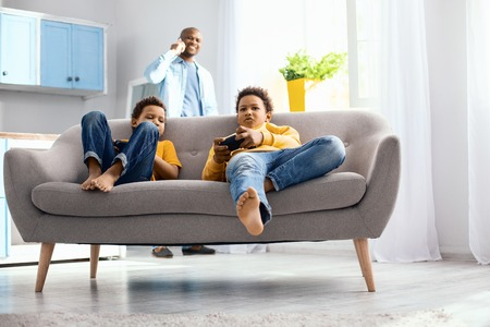 Peaceful pastime. Charming little boys sitting on the sofa and playing video game while their father having a phone conversation in the background Stock Photo