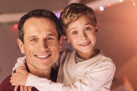 Men in the family. Nice pleasant cute boy smiling and hugging his father while looking at you Stock Photo