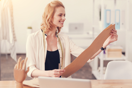 Talent noticeable. Smiling professional designer holding clothes pattern in both hands and looking at it while expressing delight Stock Photo