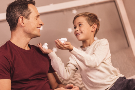 Time to shave. Cute happy positive boy holding shaving foam and smiling while looking at his father