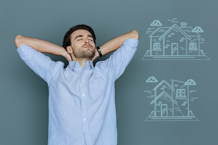 Pleasant dreams. Young tired man closing his eyes and feeling good while dreaming about owning a beautiful house
