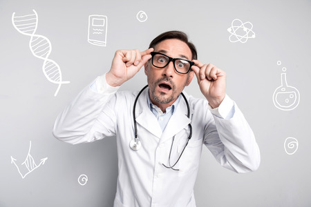 Surprised doctor. Expressive middle aged doctor wearing a white coat and opening his mouth while feeling impressed