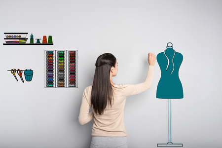 Designing clothes. Calm attentive creative tailor touching the mannequin while working