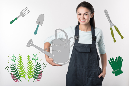 Positive gardener. Positive young experienced gardener standing with a big watering can while being at work