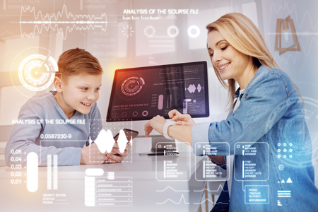 Modern gadgets. Cheerful curious boy sitting with a smartphone while his smiling mother looking at her modern smart watch