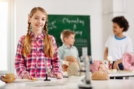 Science lesson. Nice smart girl standing at the table while having a science lesson Stock Photo