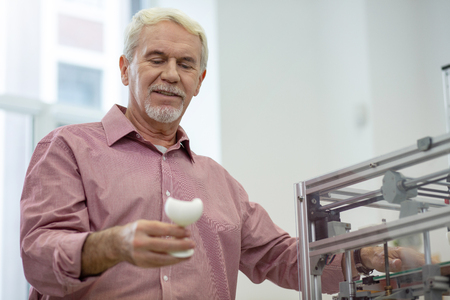 Good result. Cheerful senior man holding a 3D model and checking it out with a smile, having made it with a 3D printer