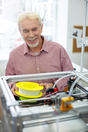 Working diligently. Pleasant senior man smiling widely while working in the office and replacing filament in the 3D printer Stock Photo