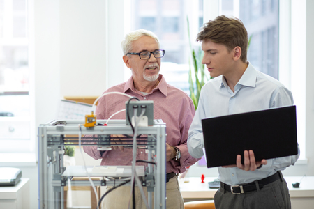 Crucial lesson. Upbeat senior engineer teaching his intern how to change 3D printer configurations while the man holding a laptop Stock Photo