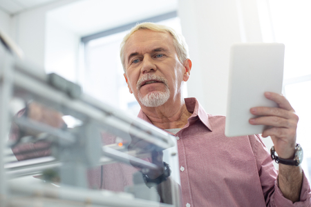 Important parameters. White-haired senior man setting up 3D printer with the help of tablet while working in the office